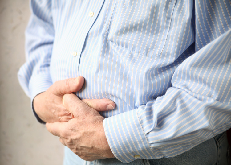 a man holds both hands to his stomach